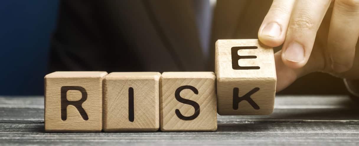 Wooden blocks spelling risk flipping k to e for rise
