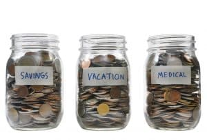 3 glass jars filled with coins, one labeled savings, 2nd labeled vacation and the 3rd medical asset based long term care guide