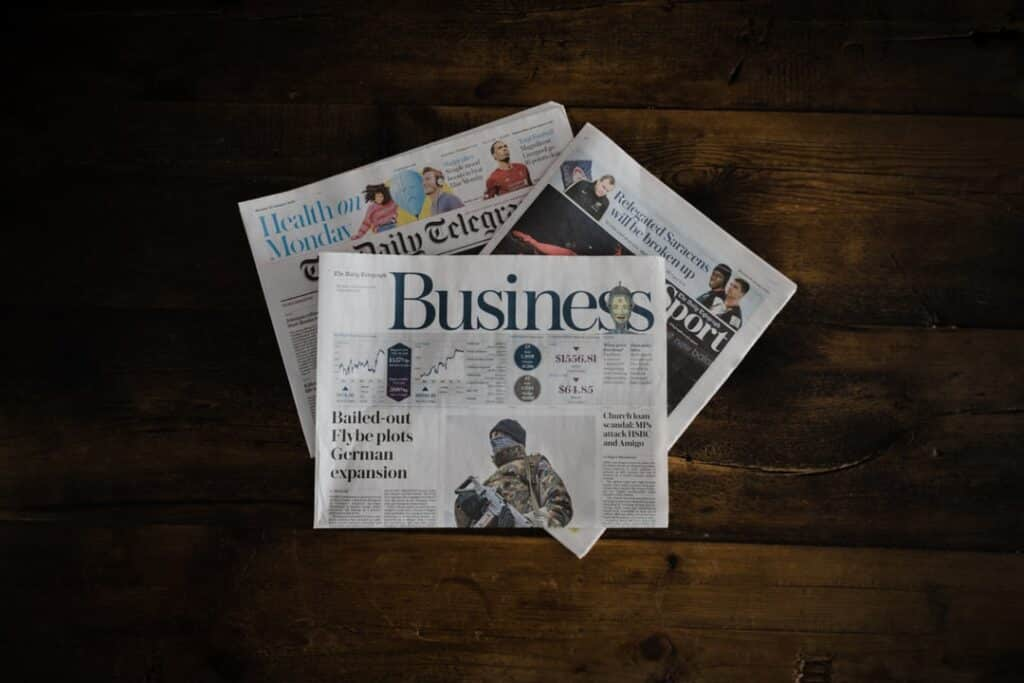 Finance Sections of Newspapers laying on dark wooden desk
