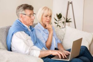 Senior couple on couch with laptop athene amplify annuity review