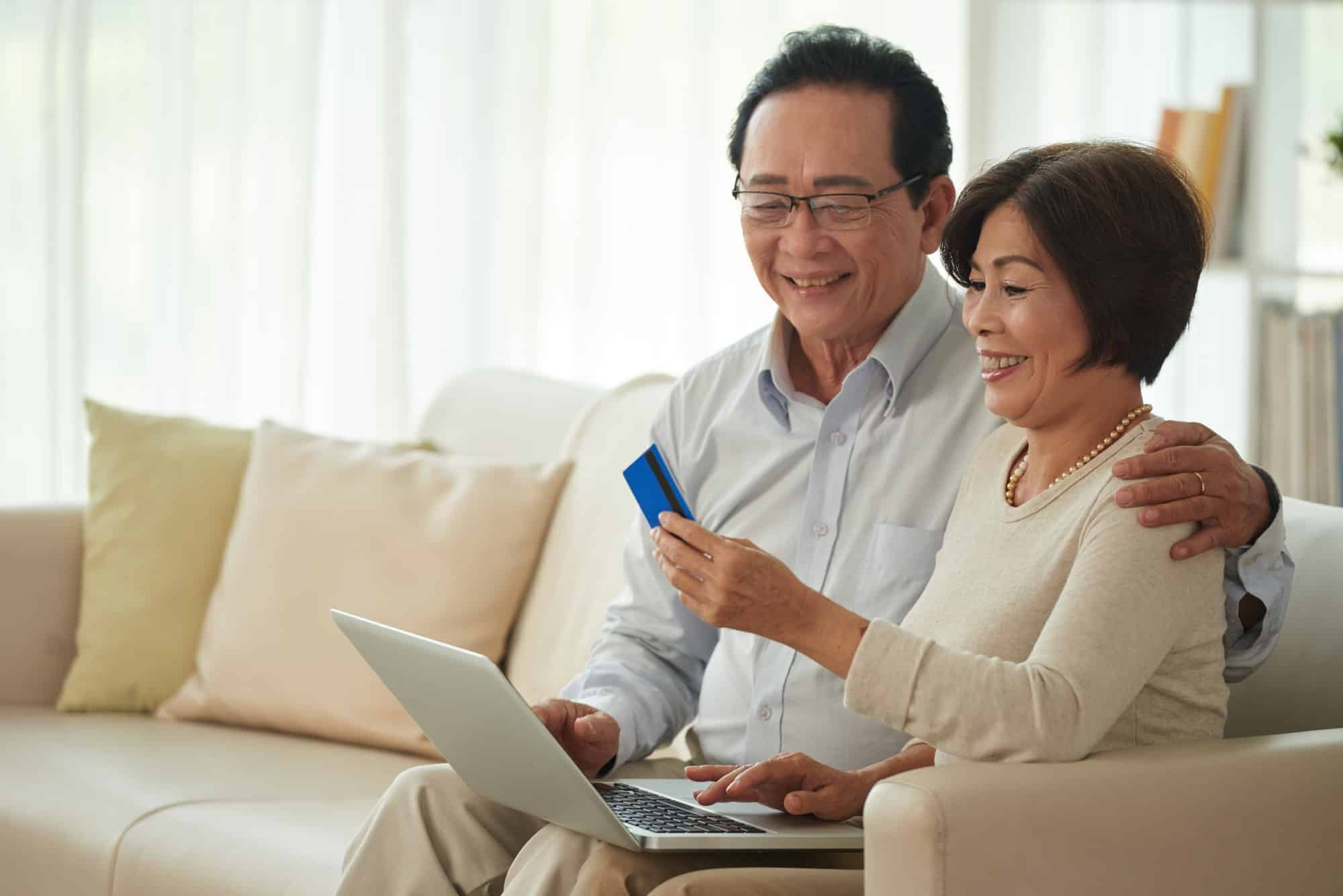 Buying an Annuity Online - Picture of Asian Couple Sitting on Couch Shopping on a Laptop
